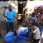 Griet en Lawrence op huisbezoek bij Lucy. Moeder en kinderen uit de buurt zijn er ook bij. Lucy kreeg naast een rolstoel ook een zetel voor thuis.