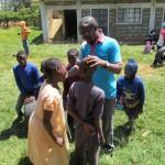Lawrence groet de lachende kinderen buiten op het gras in JAWA.