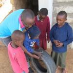 Lawrence helpt een kindje te spelen met een autoband, terwijl drie anderen met veel interesse kijken.