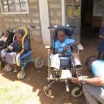 Drie kinderen zitten buiten in een rolstoel. Lawrence past de stoel van Ian aan op de gepaste lengte, ter hoogte van de voeten.