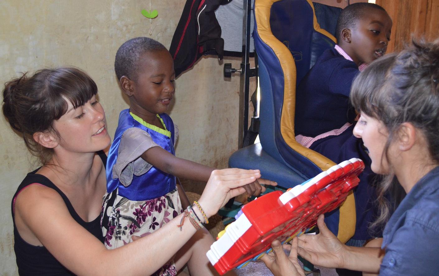 Miriam drukt een knop in met hulp van Sigrid en Annelies