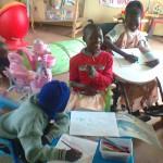 Vier kinderen binnen in JAWA. Twee van hen kleuren in kleurboeken.