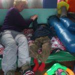 Inge strekt arm van een kindje in JAWA