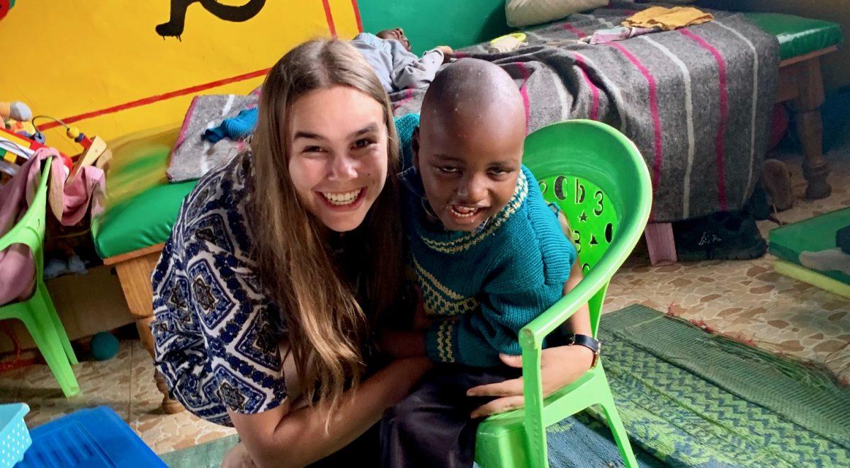 studente die samen met kindje in JAWA naar de camera lacht.